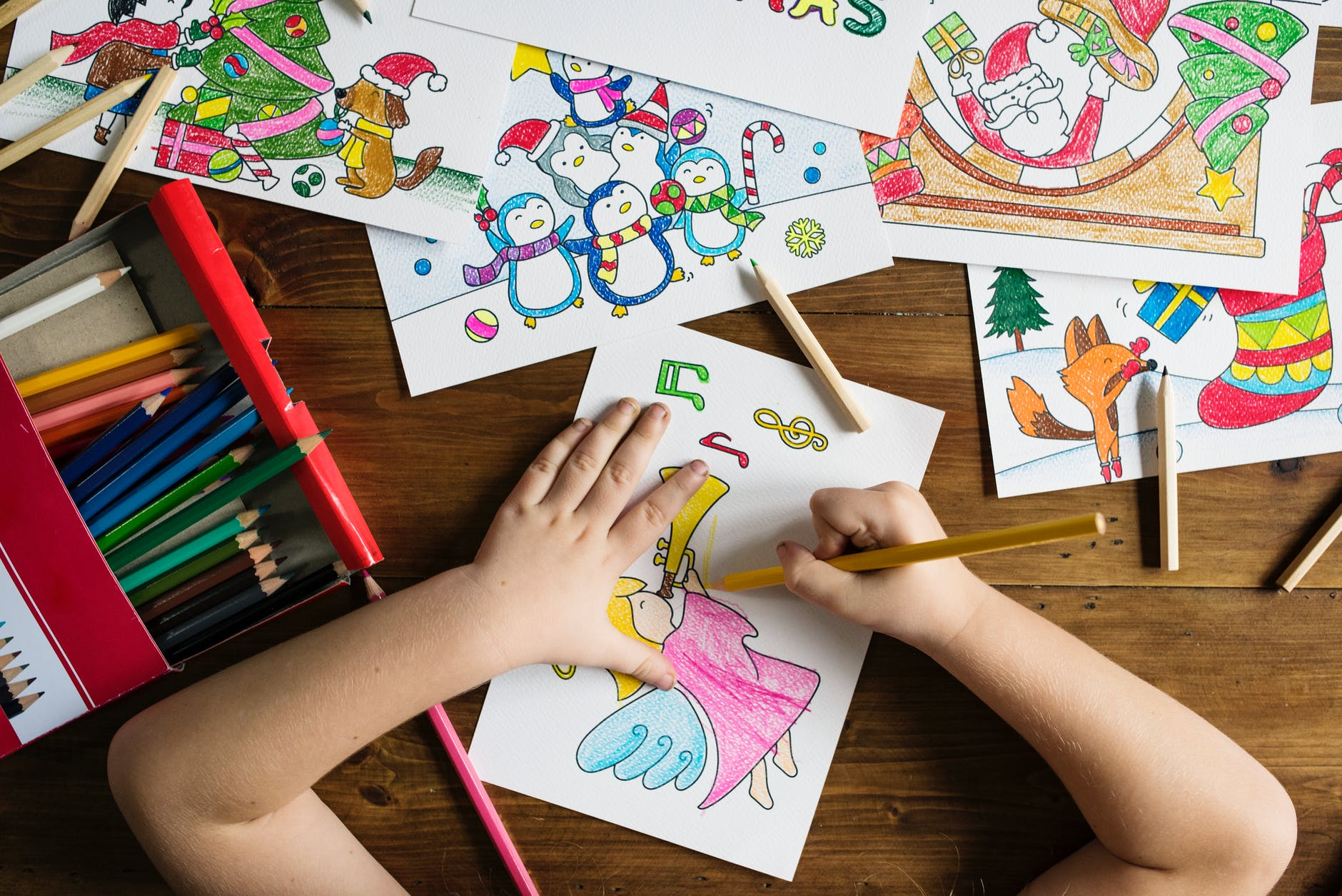 top angle photo of child holding pencil while drawing female angel playing wind instrument